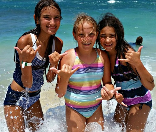 Three girls giving in the ocean giving hang loose sign at Aloha Beach Camp's Aloha Hawaii Sleepaway Summer Camp 2017