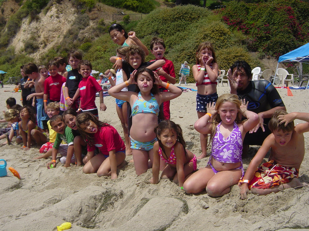 Hawaii summer camp participants making funny faces for a group photo shot on the beach.
