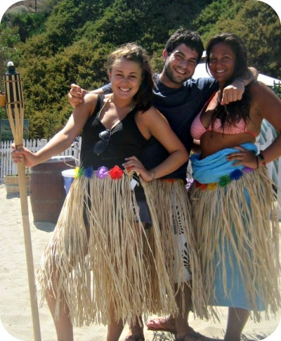 Three camp counselors standing together on the beach at Aloha Beach Camp's Hawaii summer camp program. The counselors are wearing grass skirts, colorful flower leis and holidng a Tiki Torch.