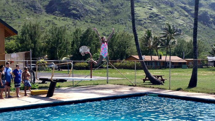 Female camper jumping off diving board in the clear blue swimming pool at summer camp in Hawaii