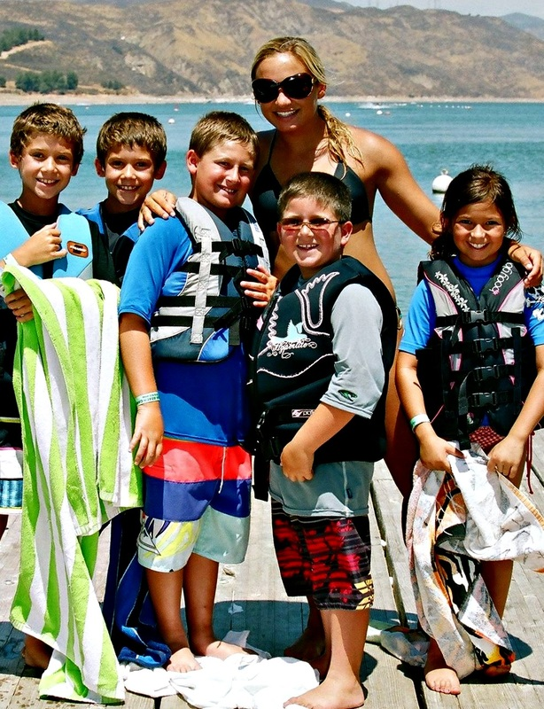 Four boys and one girl standing on the beach with their camp counselor in Hawaii.