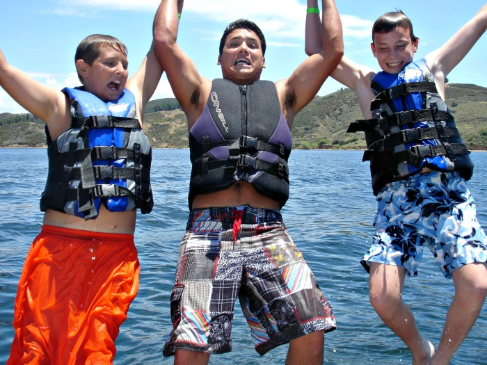 Two campers and their counselor jumping into the ocean at summer camp in Hawaii