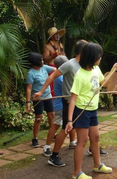 4 campers participating in Aloha Beach Camp's spear throwing activity at the Polynesian Cultural Center.